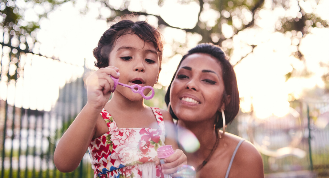 Mom blowing bubbles with daughter