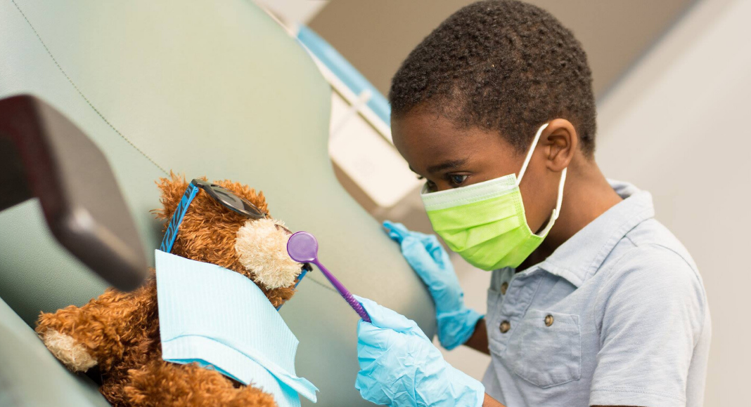 Little Boy Playing Dentist With Bear