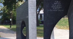 Sculpture of an obelisk with inscriptions and a carved seat on each side. Located in a city park outside a library