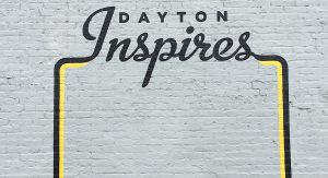 Dayton Inspires black lettering wall mural on a gray brick background