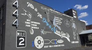 This is the day to never give up mural on dark gray wall. Several images of flight and propulsion