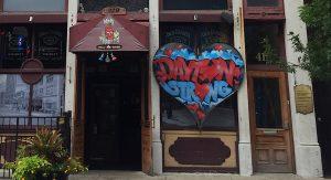 Dayton Strong graffiti lettering inside a metal heart near a store front