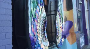 Close-up of stained glass angel wings in jewel tones