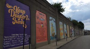 Panels of 21 murals with the first reading, Keep Dayton Funky in yellow letters on purple backdrop
